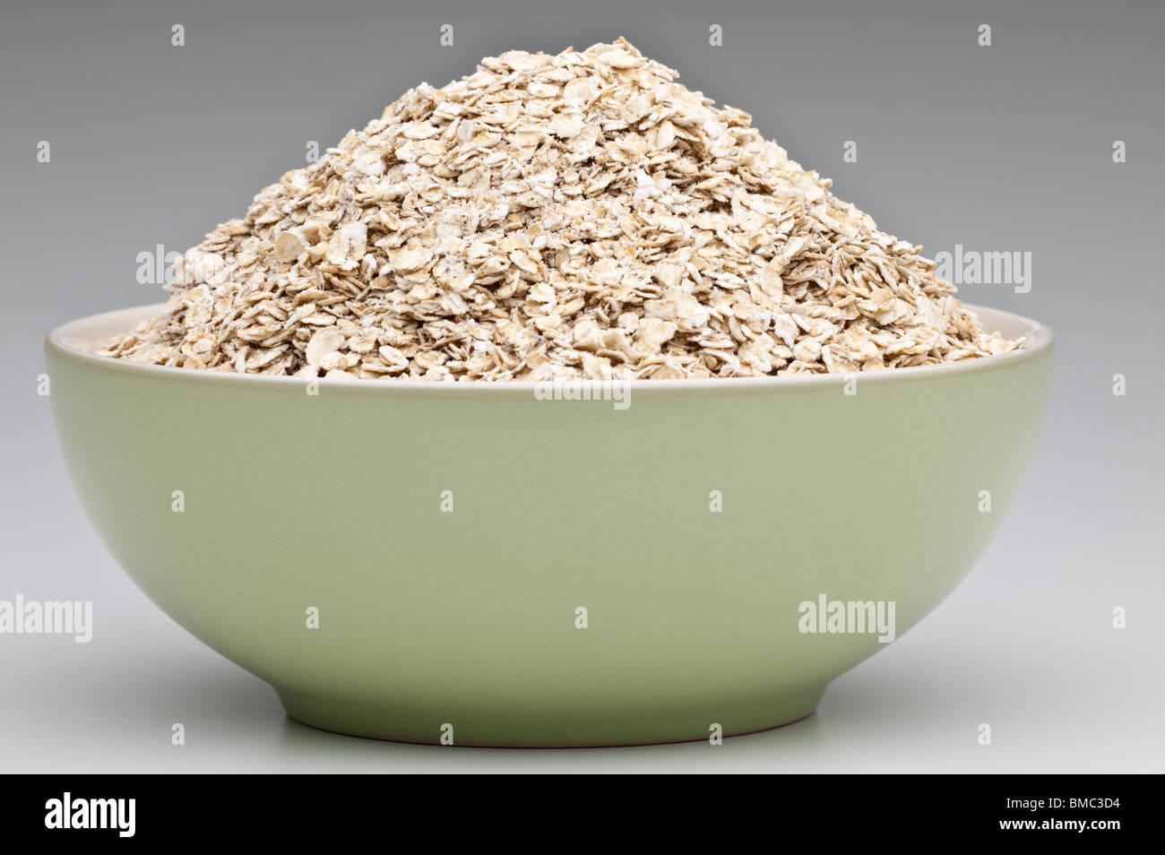 Green breakfast bowl brimming full of porridge oats - Stock Image