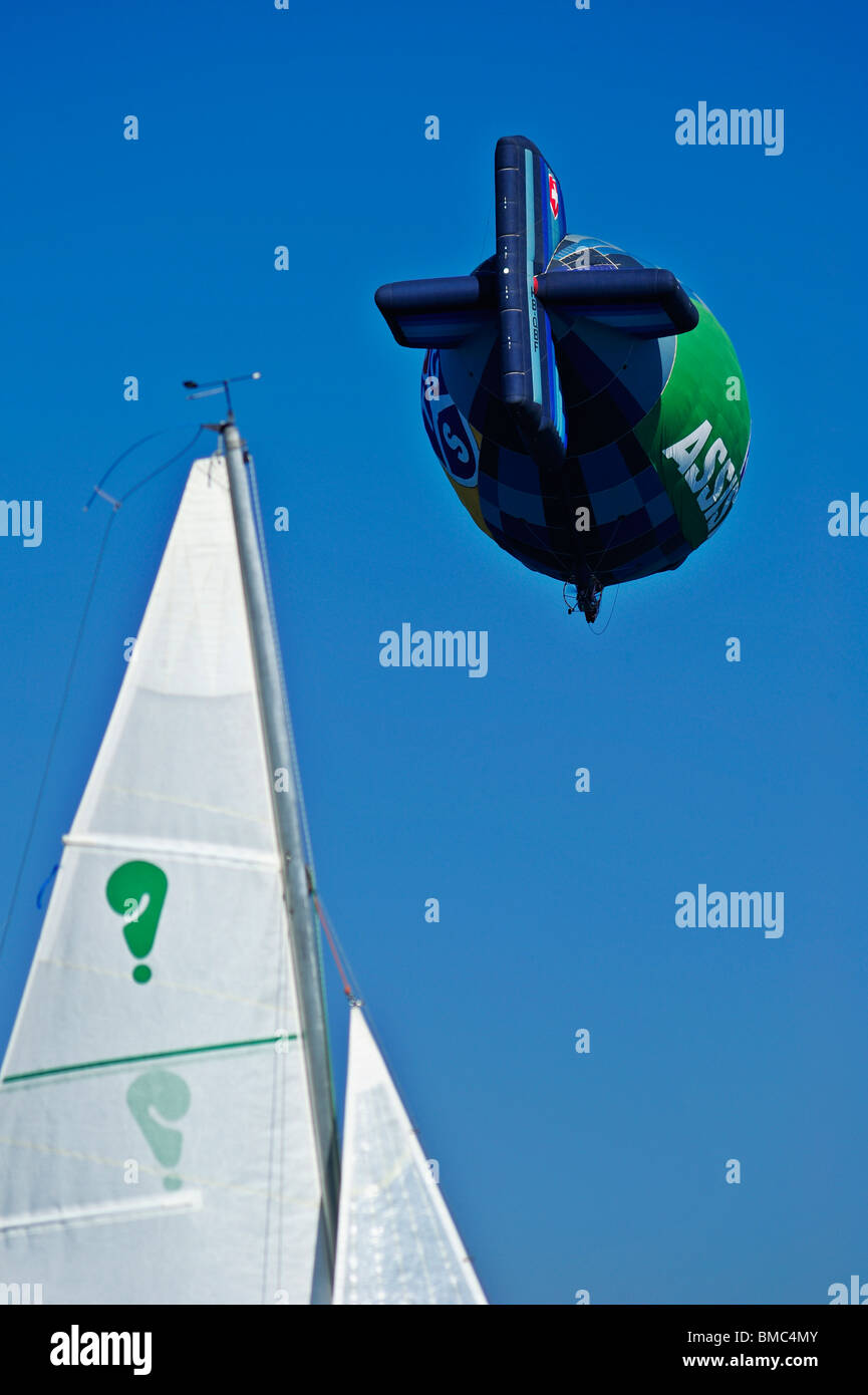 Detail of an airship passing over a sailing yacht with a question mark on its sail. Space for text lower right - Stock Image