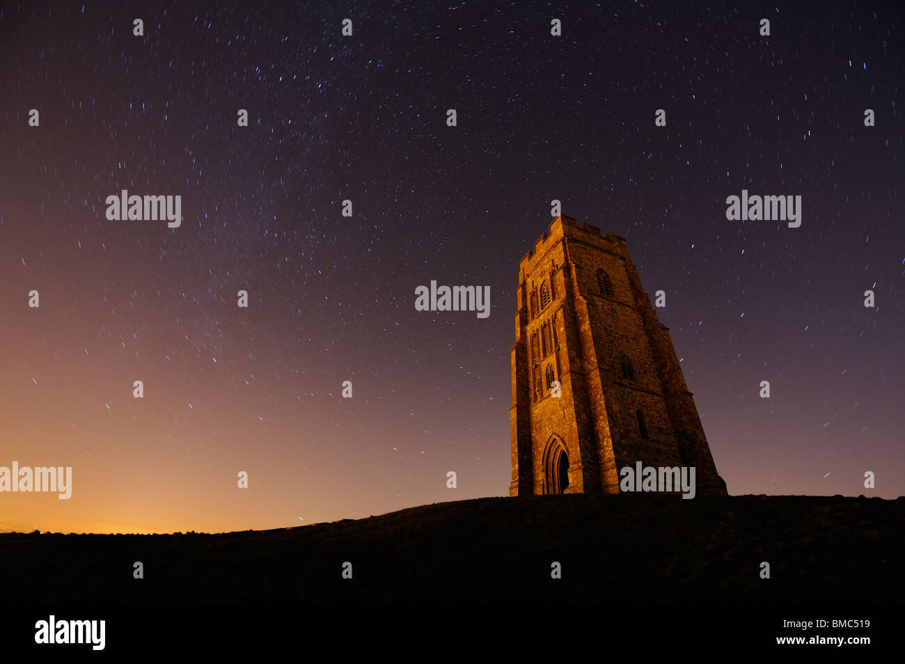 Glastonbury Tor lit by light pollution and with a starry night sky behind it. - Stock Image