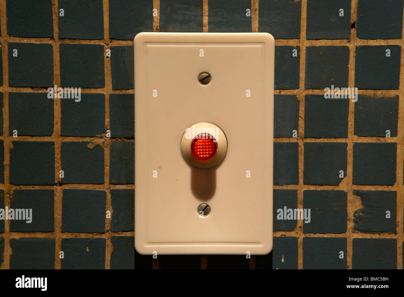 red light door buzzer button on a old tiled wall - Stock Image