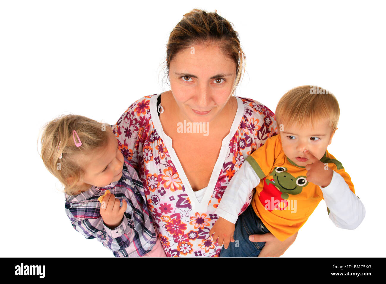 nerved mother with her children on her arms, girl eating a biscuit, boy picking his nose - Stock Image