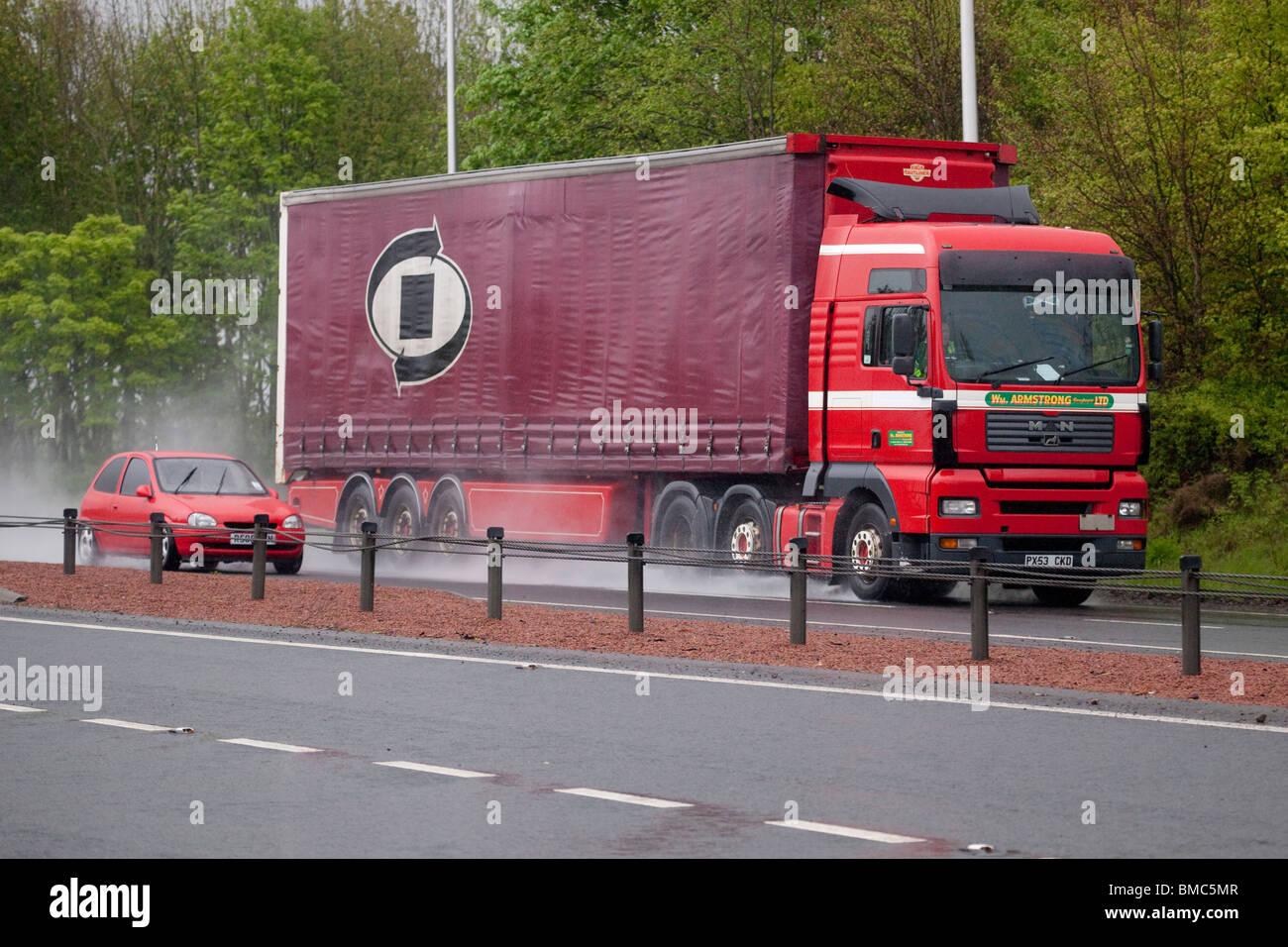 Dual carriageway road bad weather rain mist spray car overtaking a lorry rush hour traffic UK - Stock Image