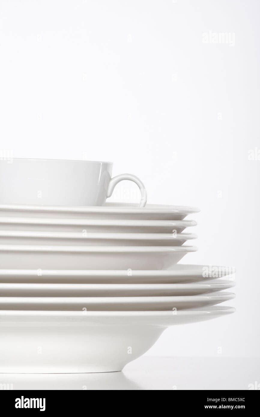 studio shot of a pile of white plates and white cup isolated on white - Stock Image