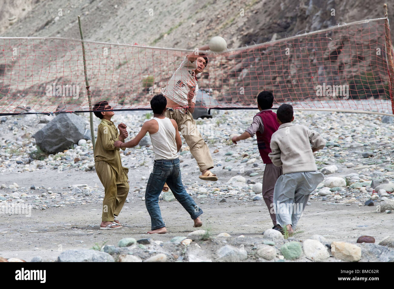 Kids playing volleyball in the Nagar Valley near Karimabad, Pakistan - Stock Image