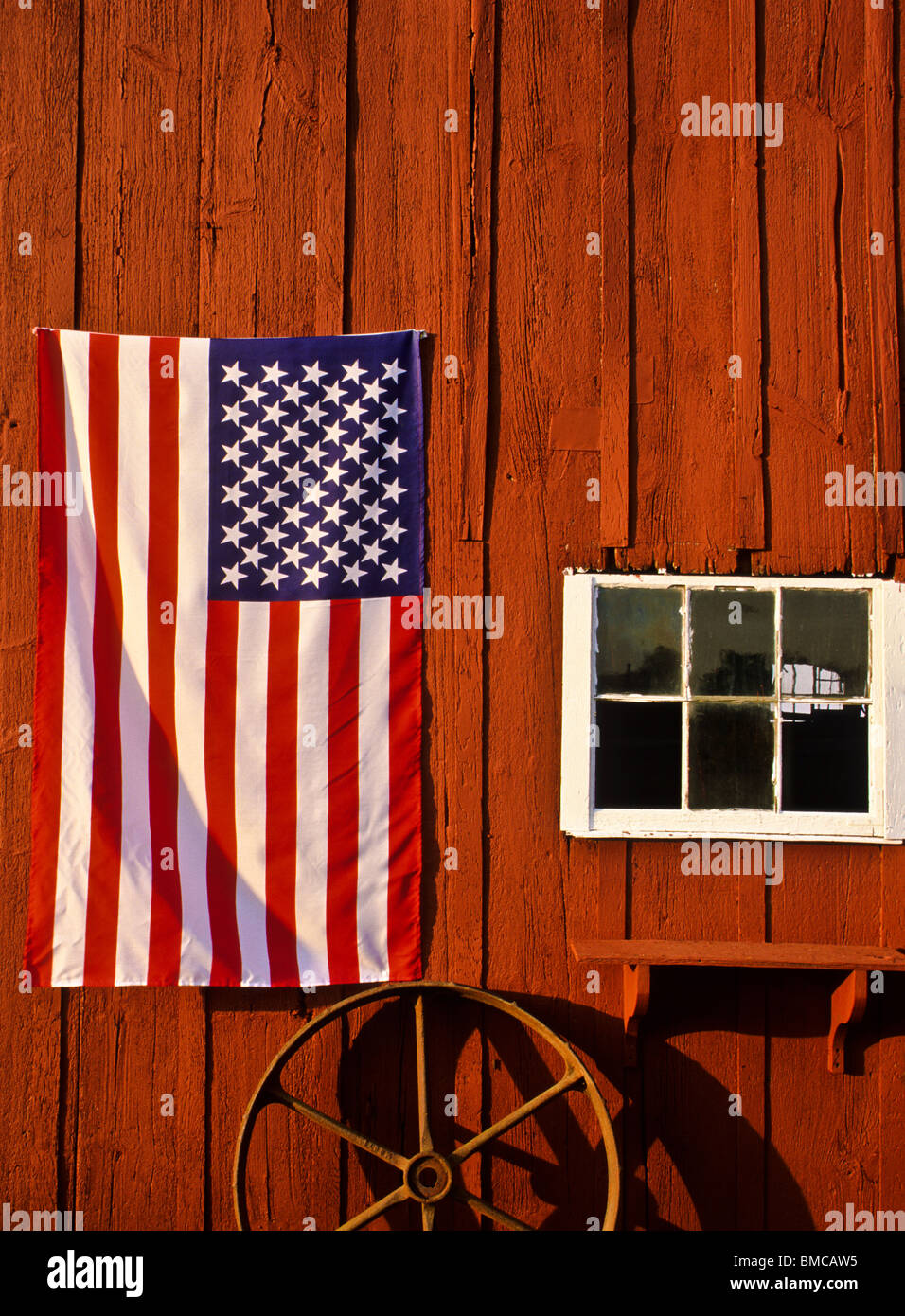 Close American Flag Vertical Up On A Vintage Red Barn With Wagon Wheel And Wooden Window Frame Ranch Middlesex County New Jersey USA
