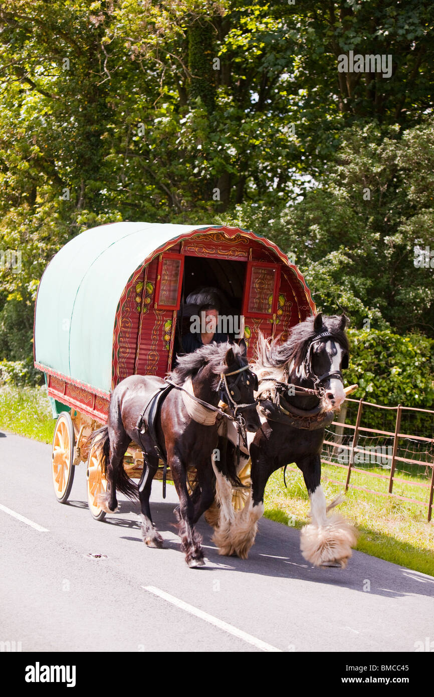 Gypsy's travelling towards the Appleby Horse Fair on a horse drawn caravan near Kirkby Lonsdale, Cumbria, UK. - Stock Image
