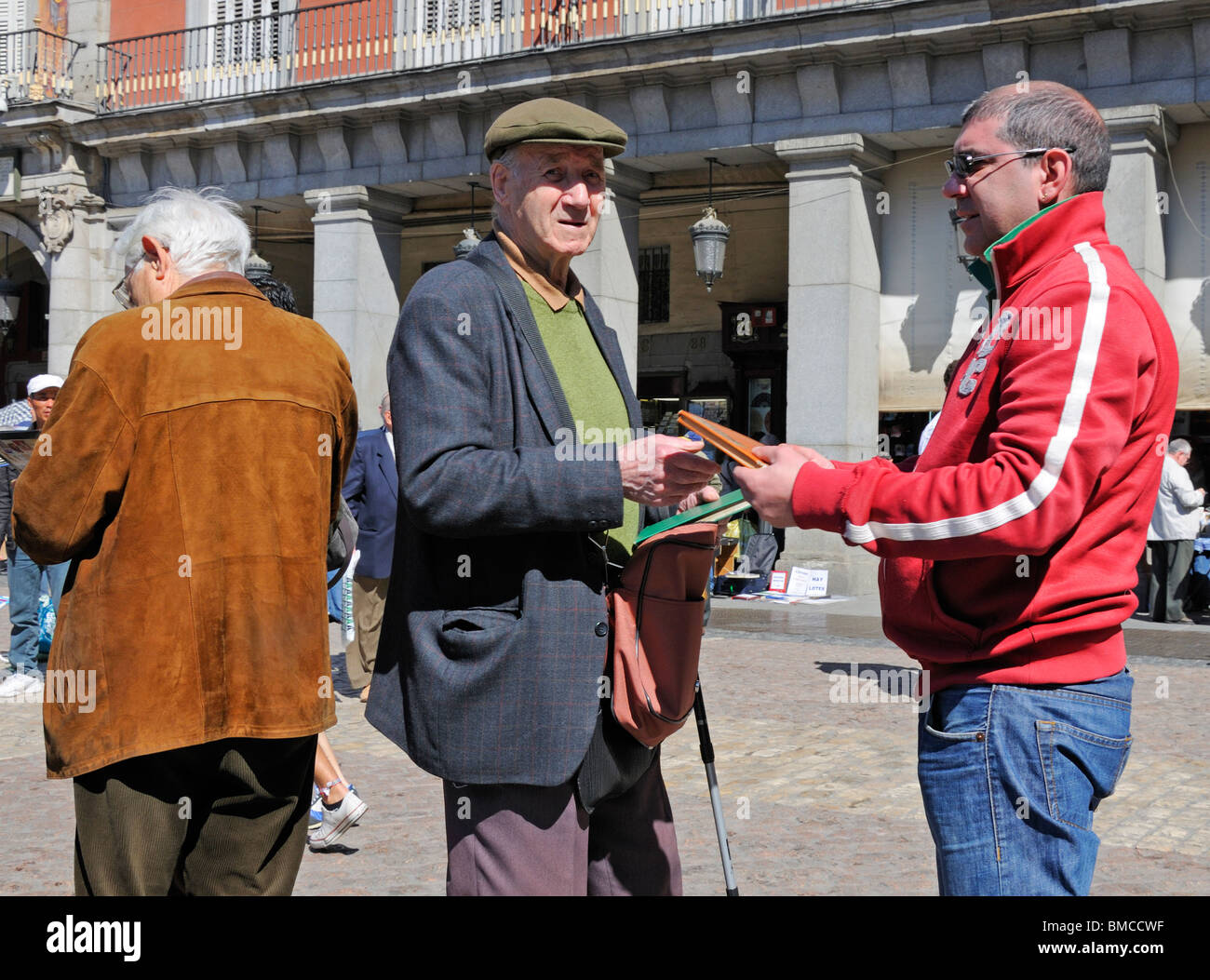 Madrid, Spain. Plaza Mayor. Men at the weekly Sunday stamp market - Stock Image