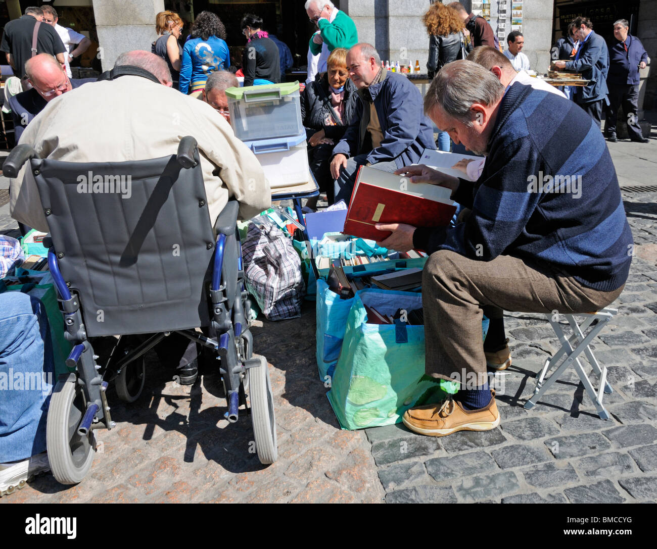 Madrid, Spain. Plaza Mayor. Men at the weekly Sunday stamp market, one in a wheelchair - Stock Image