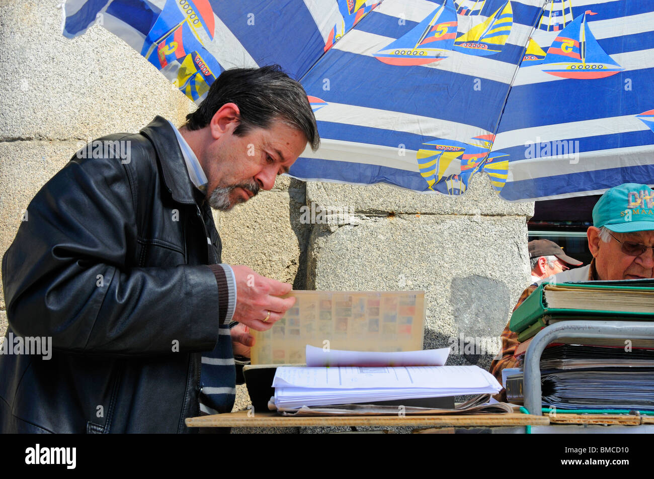 Madrid, Spain. Plaza Mayor. Customer and stallholder at weekly Sunday stamp market - Stock Image