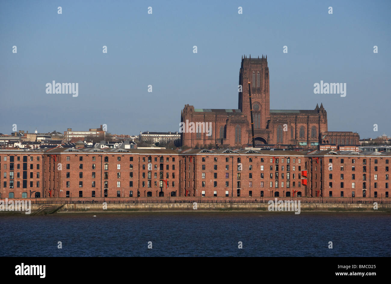 former warehouses on liverpool waterfront shoreline with liverpool anglican cathedral in the background merseyside - Stock Image