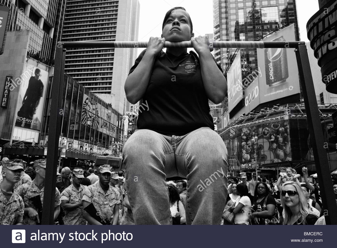 Sarrah Mitchell age 26 hangs from a chin up pole during training contests organized by Fleet Week in Times Square - Stock Image