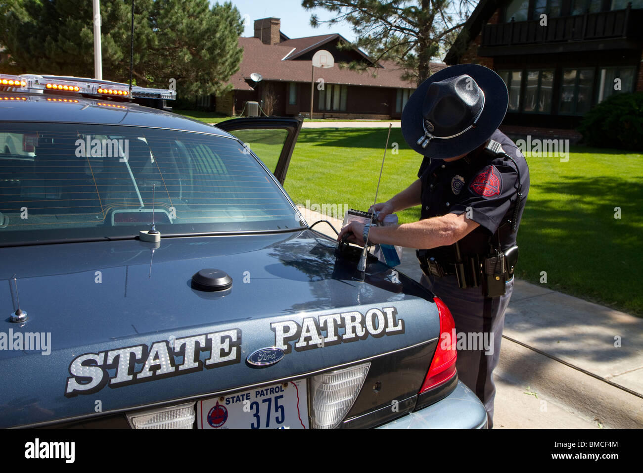 Nebraska State Trooper cleaning the Automated License Plate Reader that is mounted on his police cruiser. - Stock Image