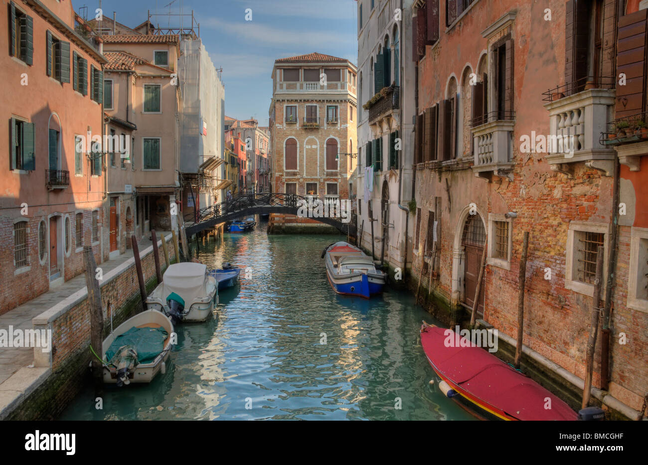 Backstreet Canal in Venice, Italy, showing beautiful soft light reflected on water and buildings - Stock Image