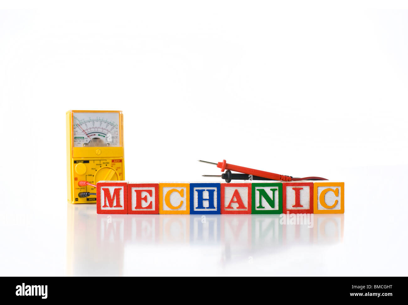 Colorful children's blocks spelling MECHANIC with a test meter - Stock Image