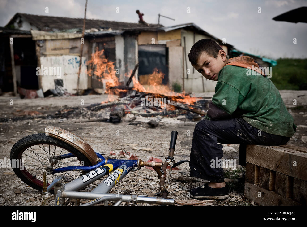 A Roma boy sitting in front of barrack and waiting for authorities dislocate his family. - Stock Image