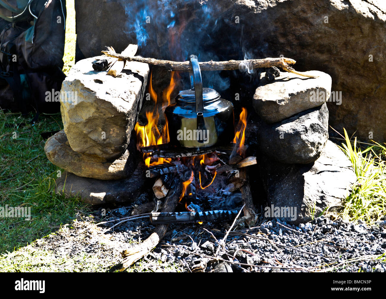 Old established conventional method of arranged stones making into stove structure with wood burning fire for cooking - Stock Image