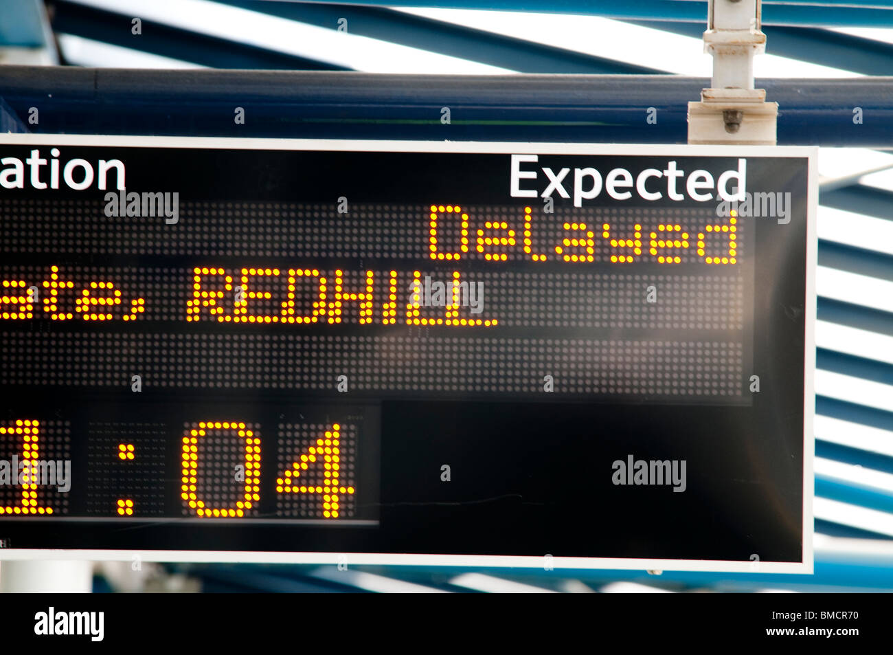 Delayed sign at a train station - Stock Image