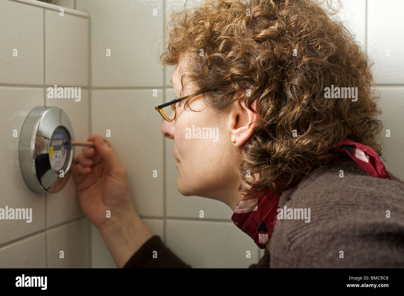 Homeowner taking a reading from a water meter - Stock Image