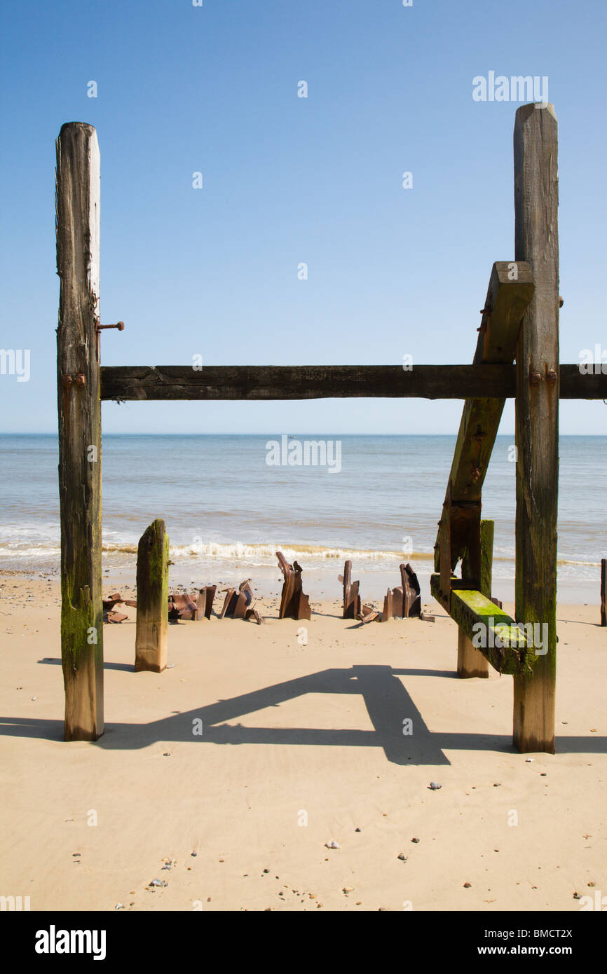 Wooden posts casting a shadow of number 4 on the beach. - Stock Image