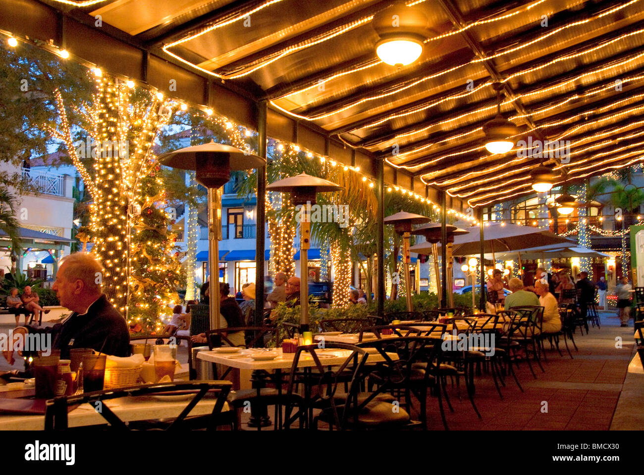 Patio restaurant overlooking a square on 5th Avenue South during Christmas festivities in Naples, Florida, USA - Stock Image
