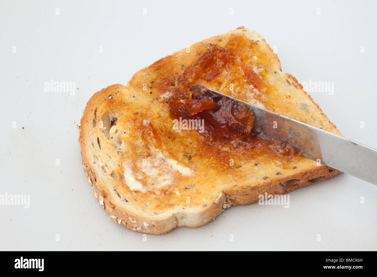 Spreading marmalade on a slice of toast with melted butter using a knife - Stock Image