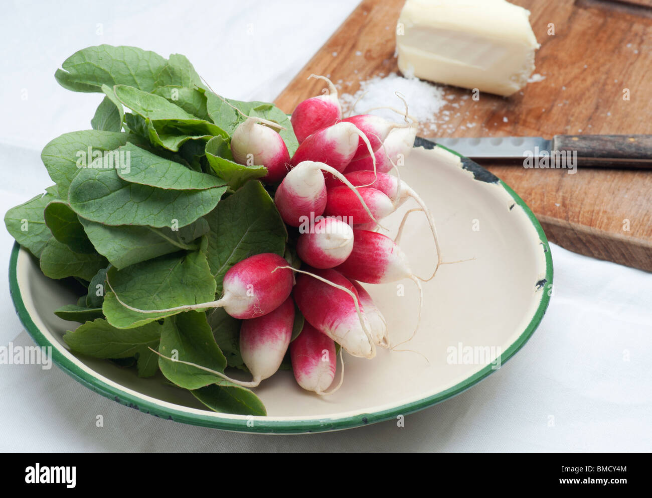 Fresh Radishes In An Enamel Dish, With Butter, Salt and A Knife In The Background Stock Photo