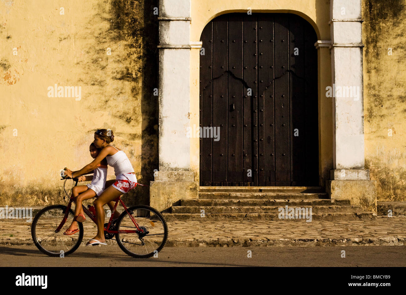 Two girls ride a bicycle in Remedios, Cuba on Thursday July 17, 2008. - Stock Image