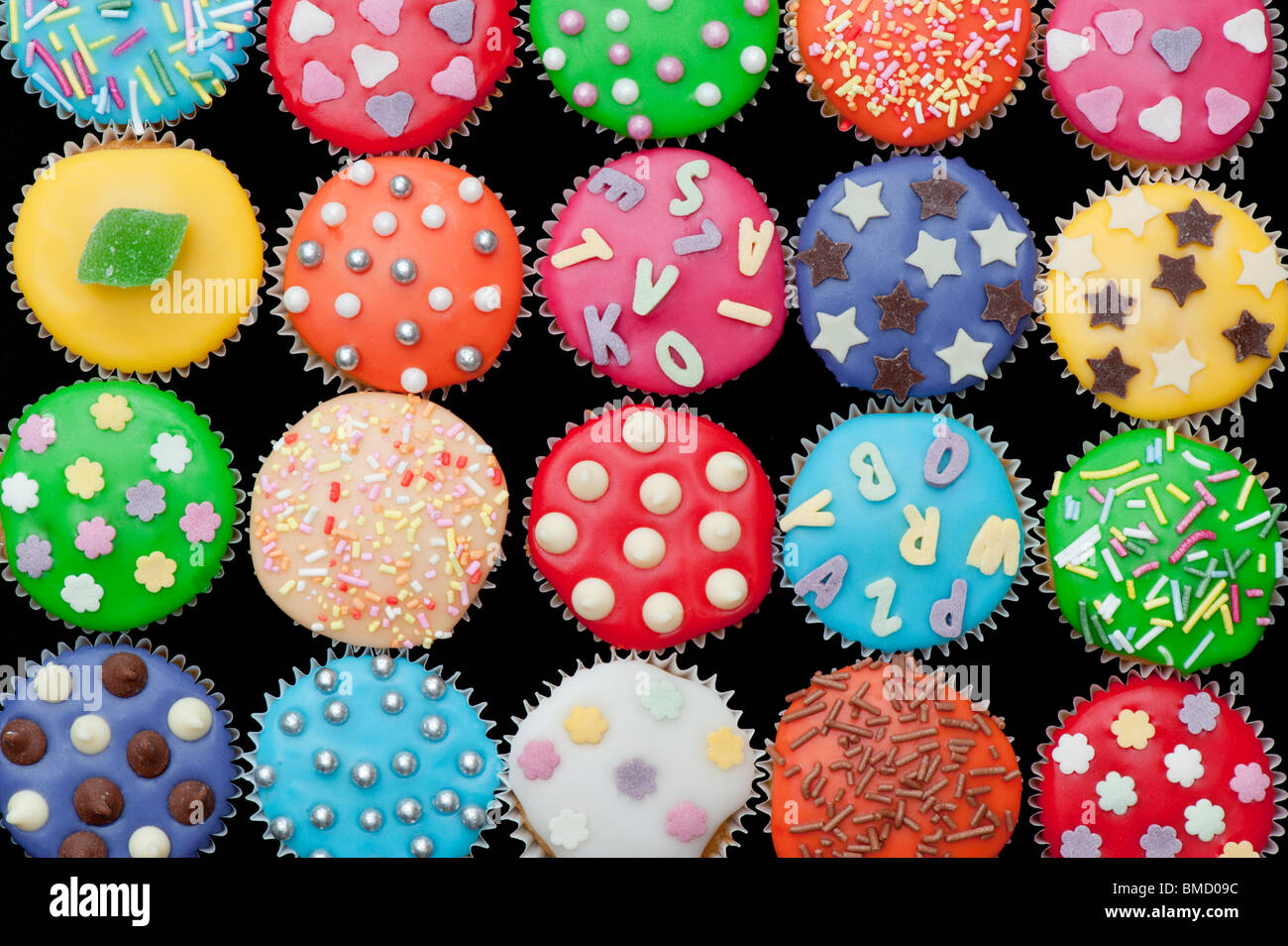 Colourful mini cupcakes on a black background - Stock Image