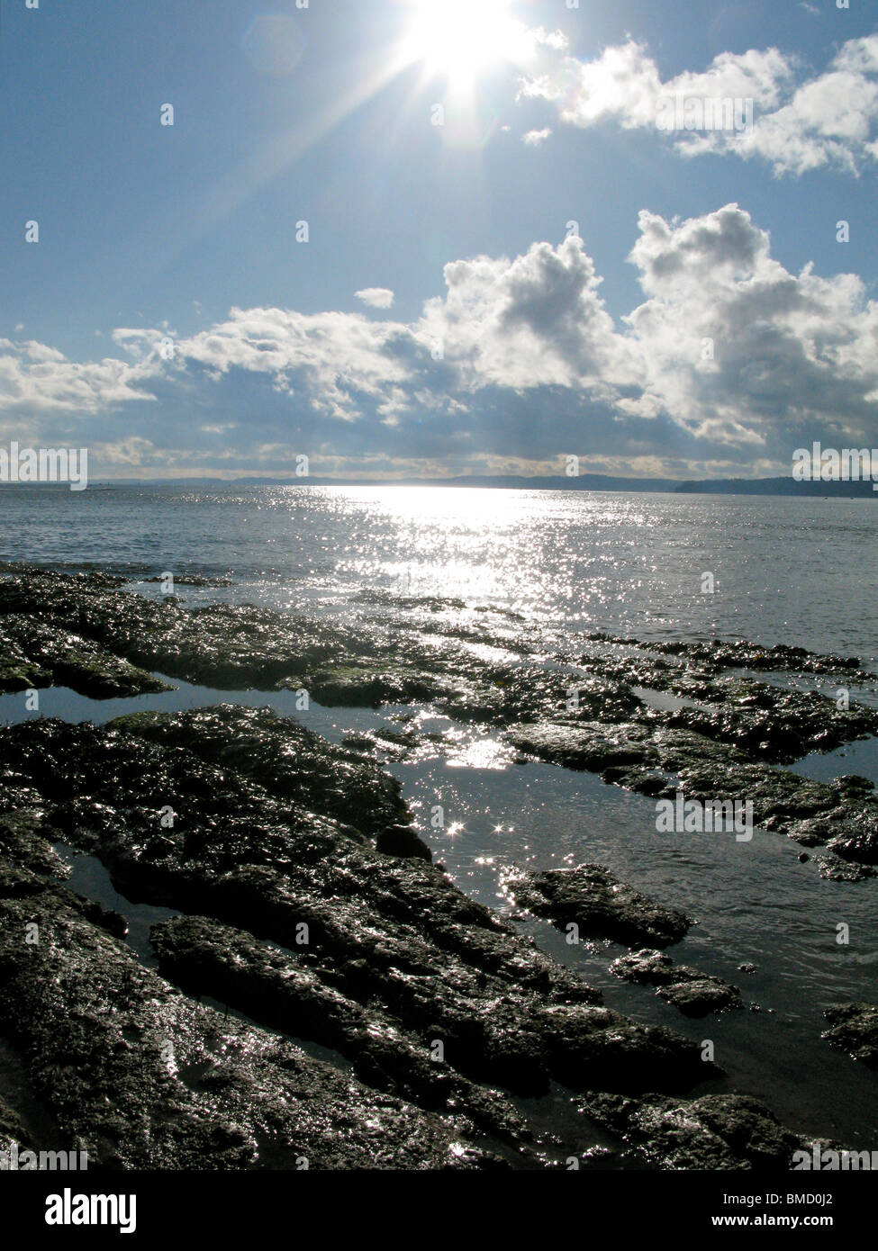 The sun shines on some beach rocks and the sea. The sky is blue with patches of cloud. Stock Photo