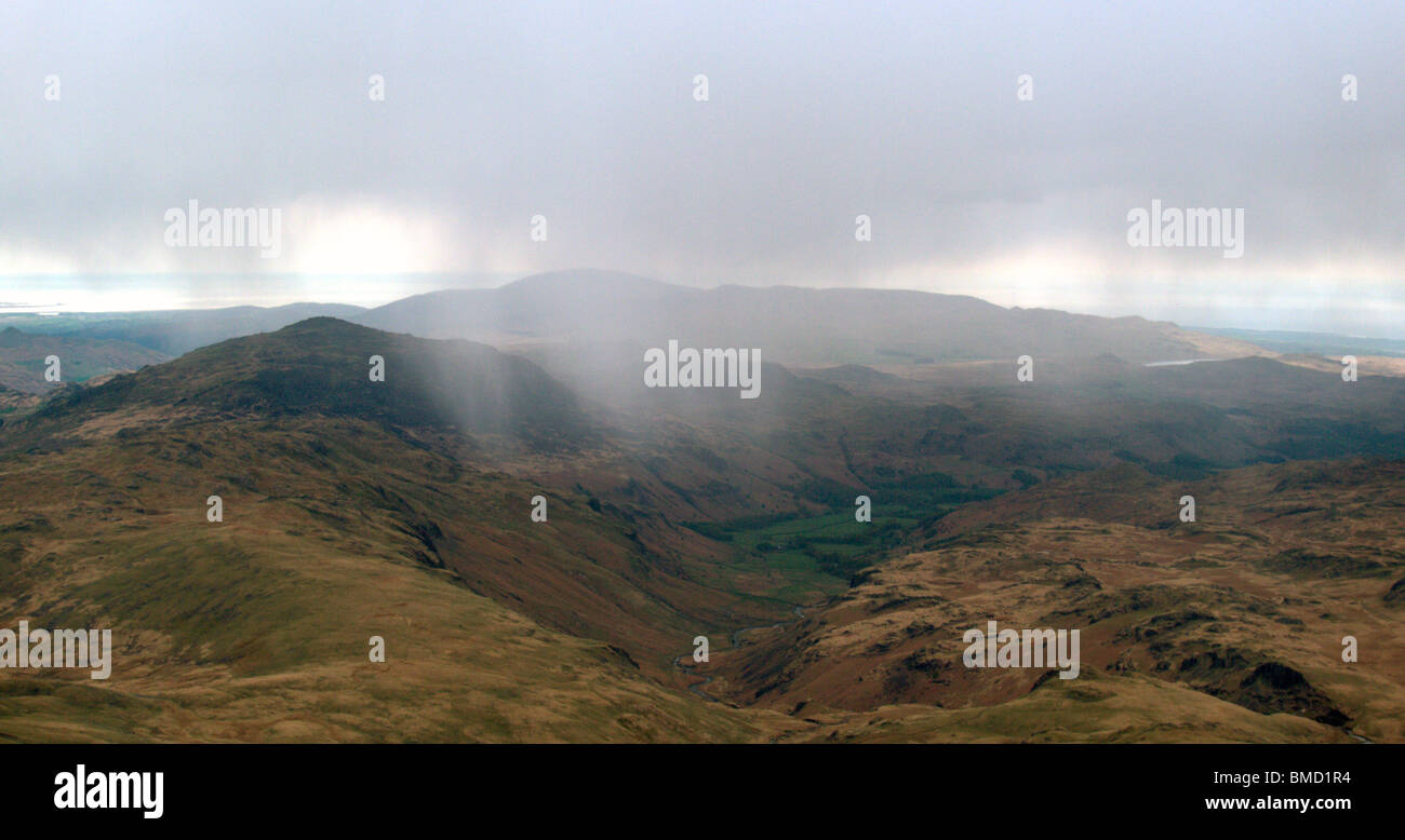 Rain sweeping over Harter Fell to Eskdale viewed from Bow Fell, Cumbria, UK. - Stock Image
