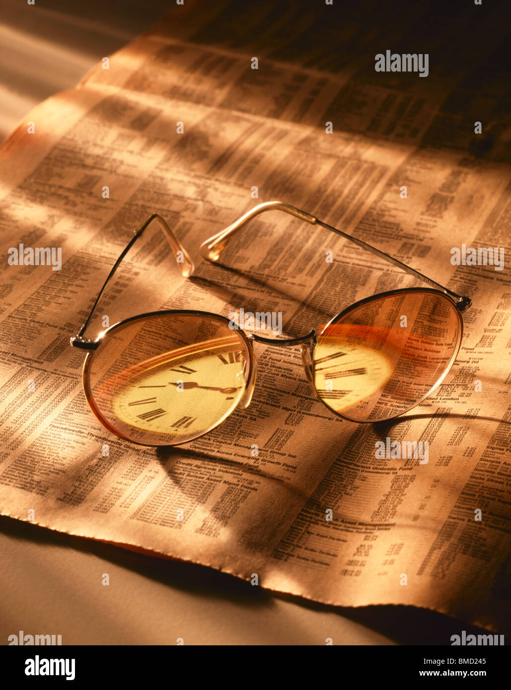Glasses on the Financial Times with Reflected Clock Stock Photo