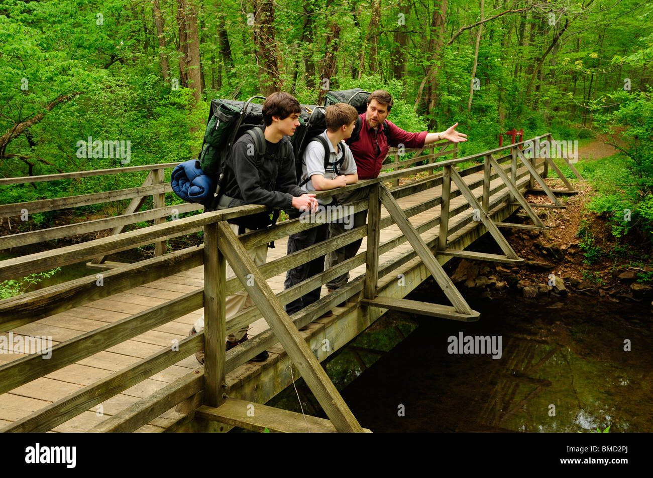 A father and two sons share a moment of camaraderie on a bridge along a hiking trail - Stock Image