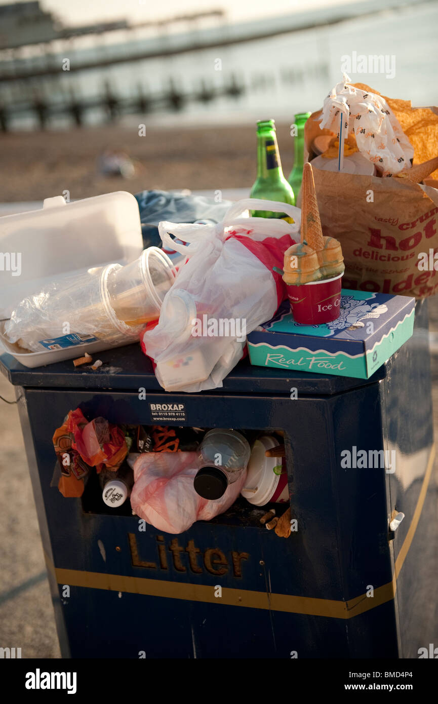 Overflowing rubbish bin at the seaside at the end of a summer day, UK - Stock Image