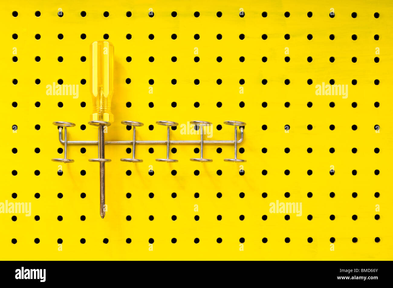 One yellow Phillips screwdriver sits in a rack on a yellow pegboard. - Stock Image