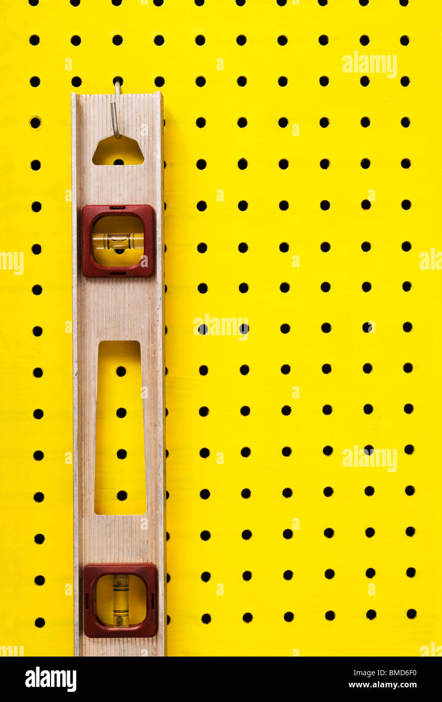 Old level hangs from a hook on yellow pegboard. - Stock Image