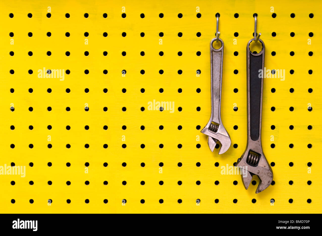 Pair of metal wrenches hang together off of hooks on yellow pegboard. - Stock Image