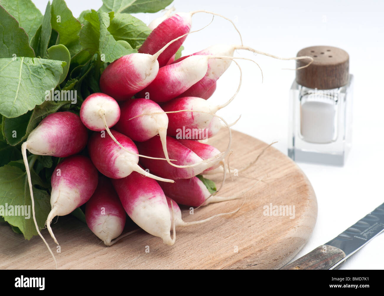 A Bunch Of Fresh French Breakfast Radish On A Wooden Chopping Board, With A Salt Pot and knife, On A White Background Stock Photo