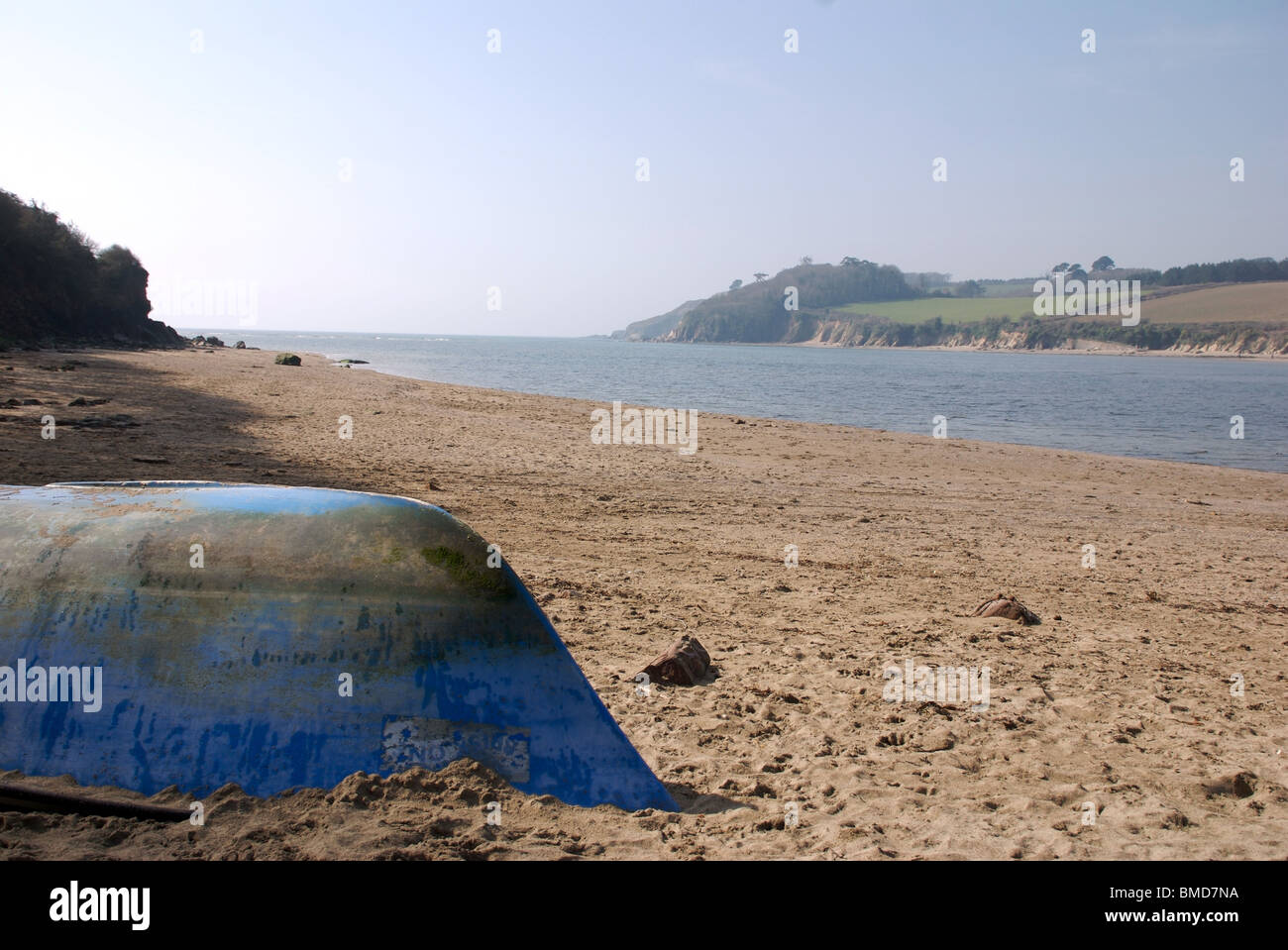 Upturned blue boat and bicycle wheel, Erme estuary, near Kingston, South Hams, Devon, UK - Stock Image