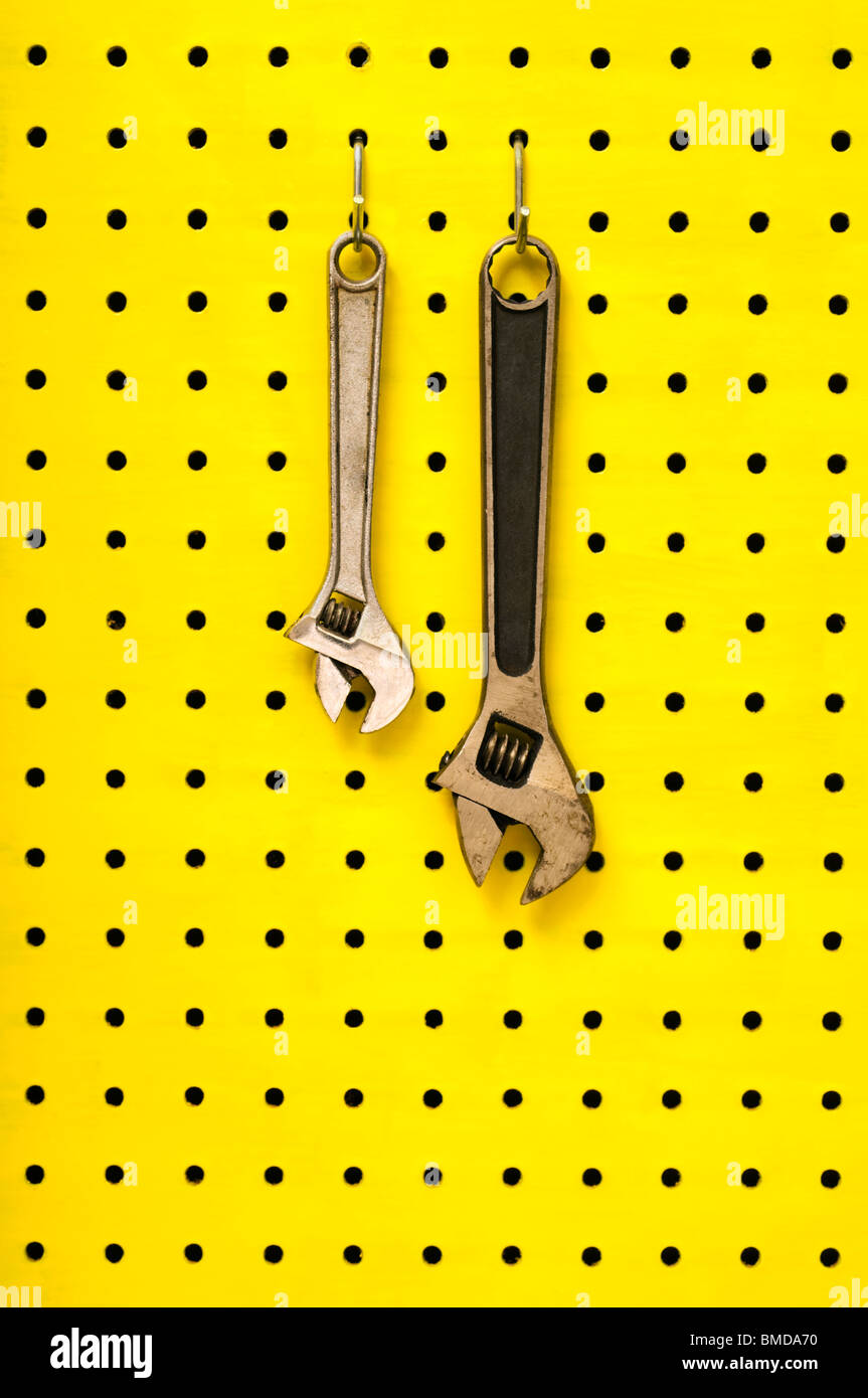 Pair of metal wrenches (spanners) hang together off of hooks on yellow pegboard. - Stock Image