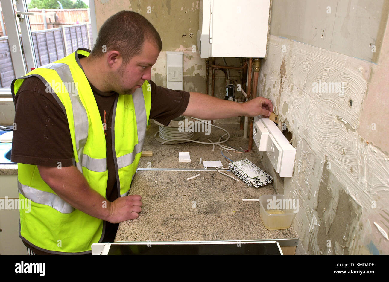 A workman fits electrical sockets in a housing association kitchen UK Stock Photo