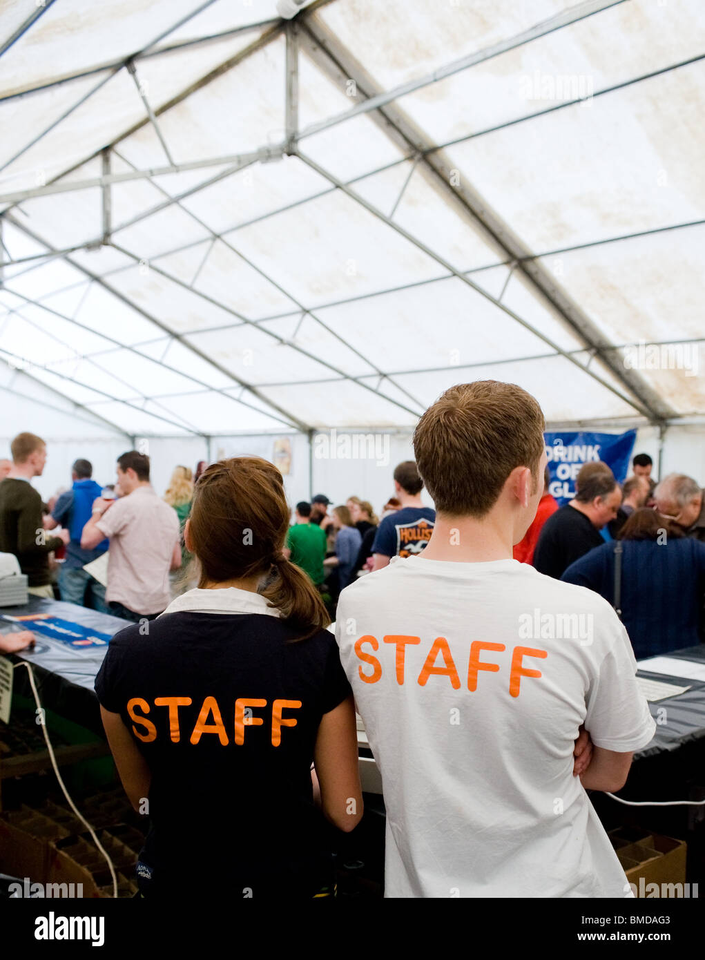 Staff working behind the bar at the Hoop Pub Beer Festival in Stock in Essex. - Stock Image