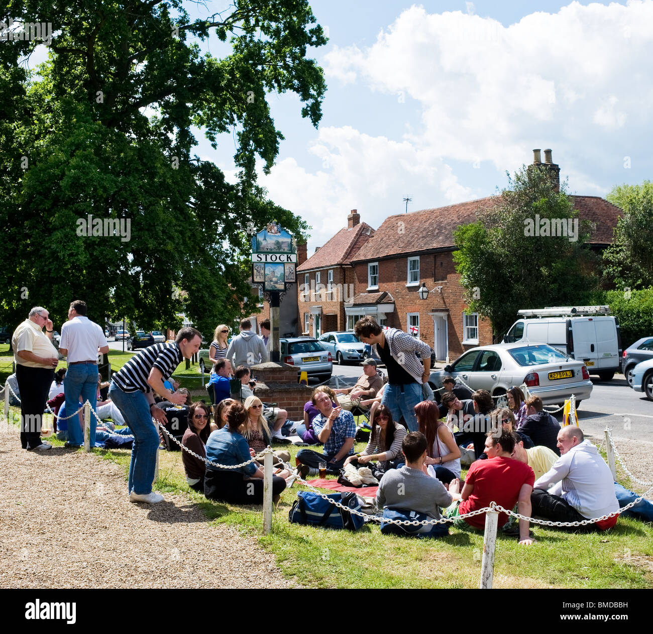 People sitting on the grass in Stock village in Essex.  Photo by Gordon Scammell - Stock Image