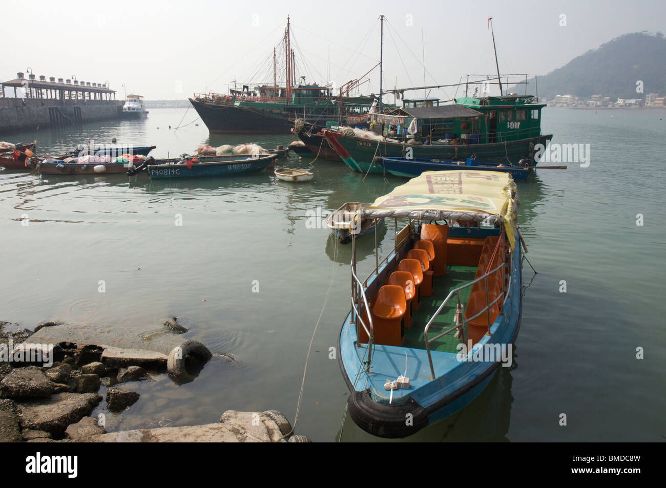 Fishing boats and ferry and tourist boat in Tai O harbour on Lantau Island near Hong Kong in China - Stock Image
