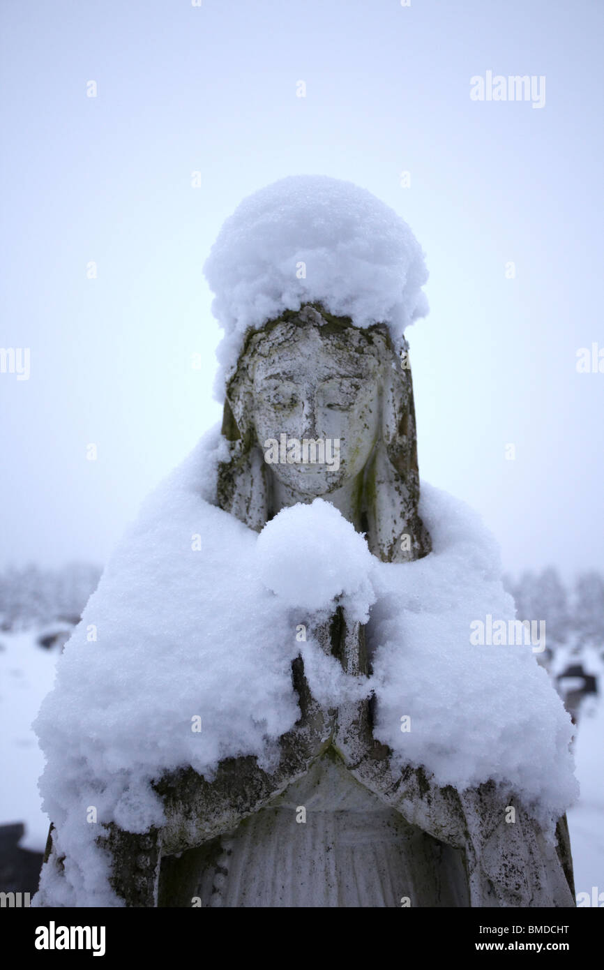 Snow covered Angel tombstone - Stock Image