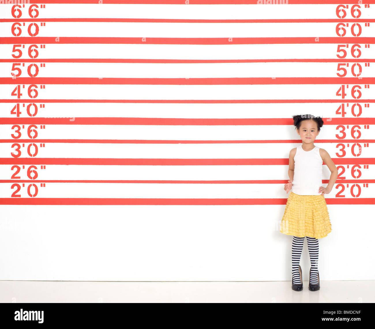 Girl in high heels by growth chart - Stock Image