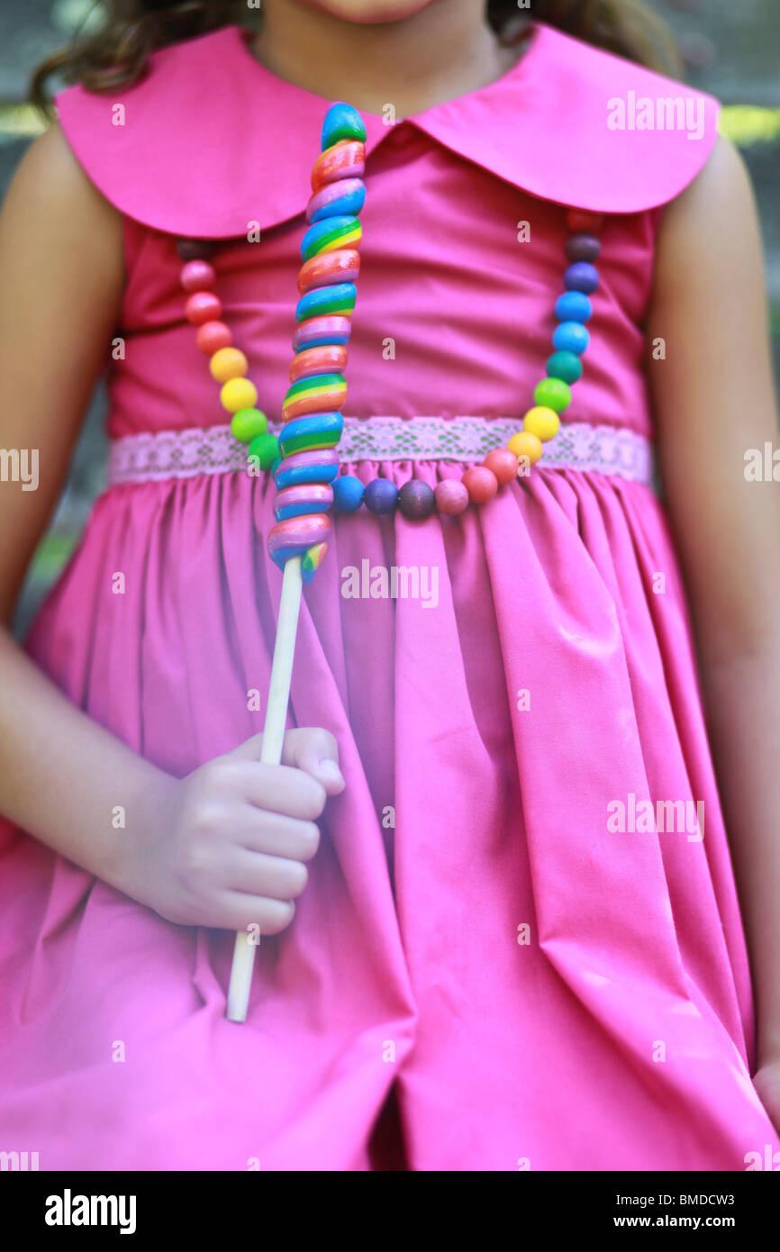 Girl in magenta dress holding lollipop - Stock Image