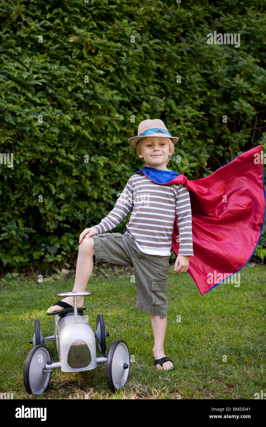 Boy in cape with toy car - Stock Image