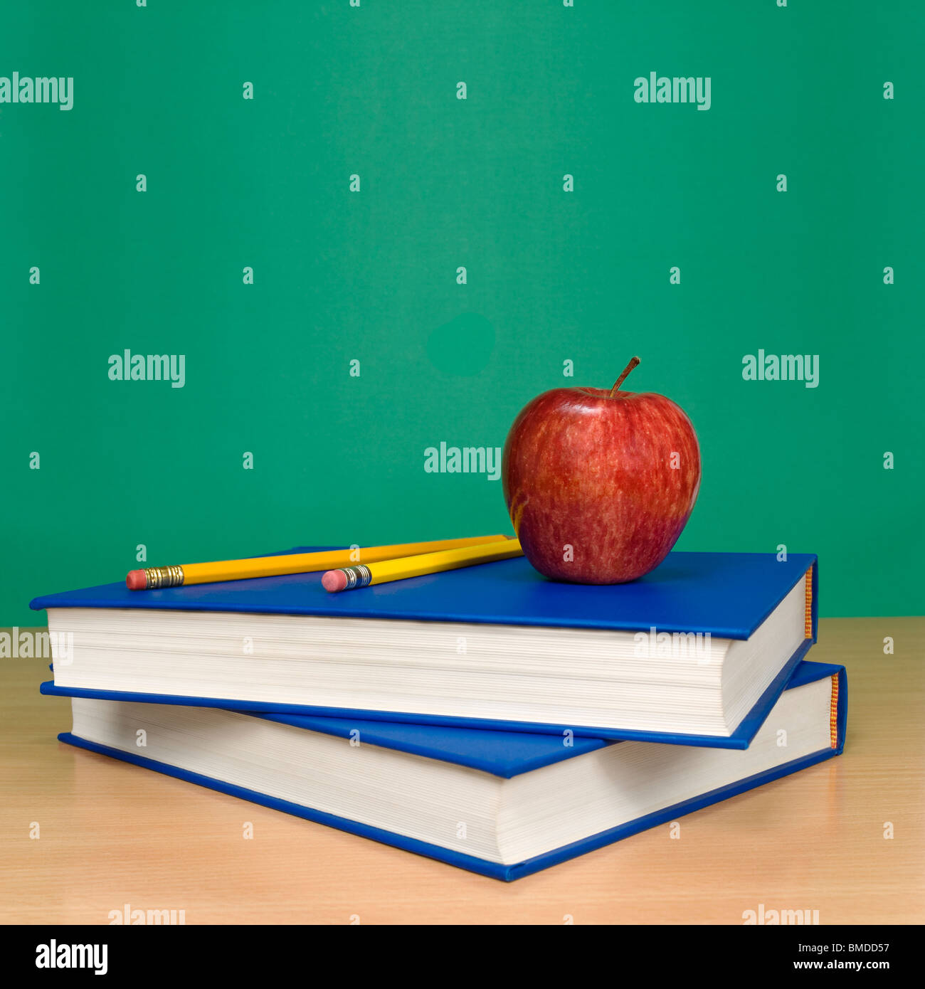 Blank chalkboard. Books, pencils and an apple on foreground. - Stock Image