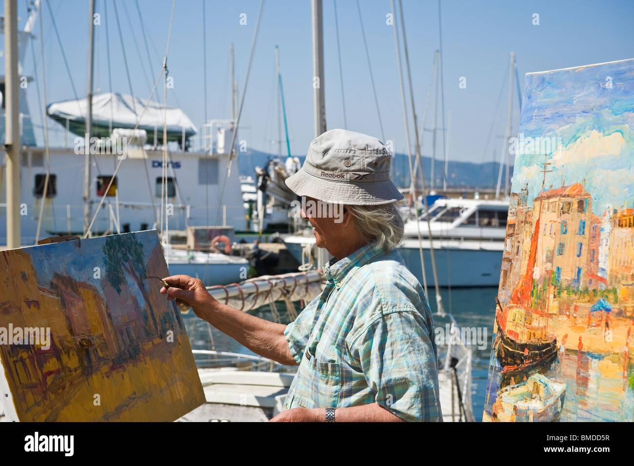 Artiste Peintre St Tropez street artist painting in harbor, saint tropez, france stock