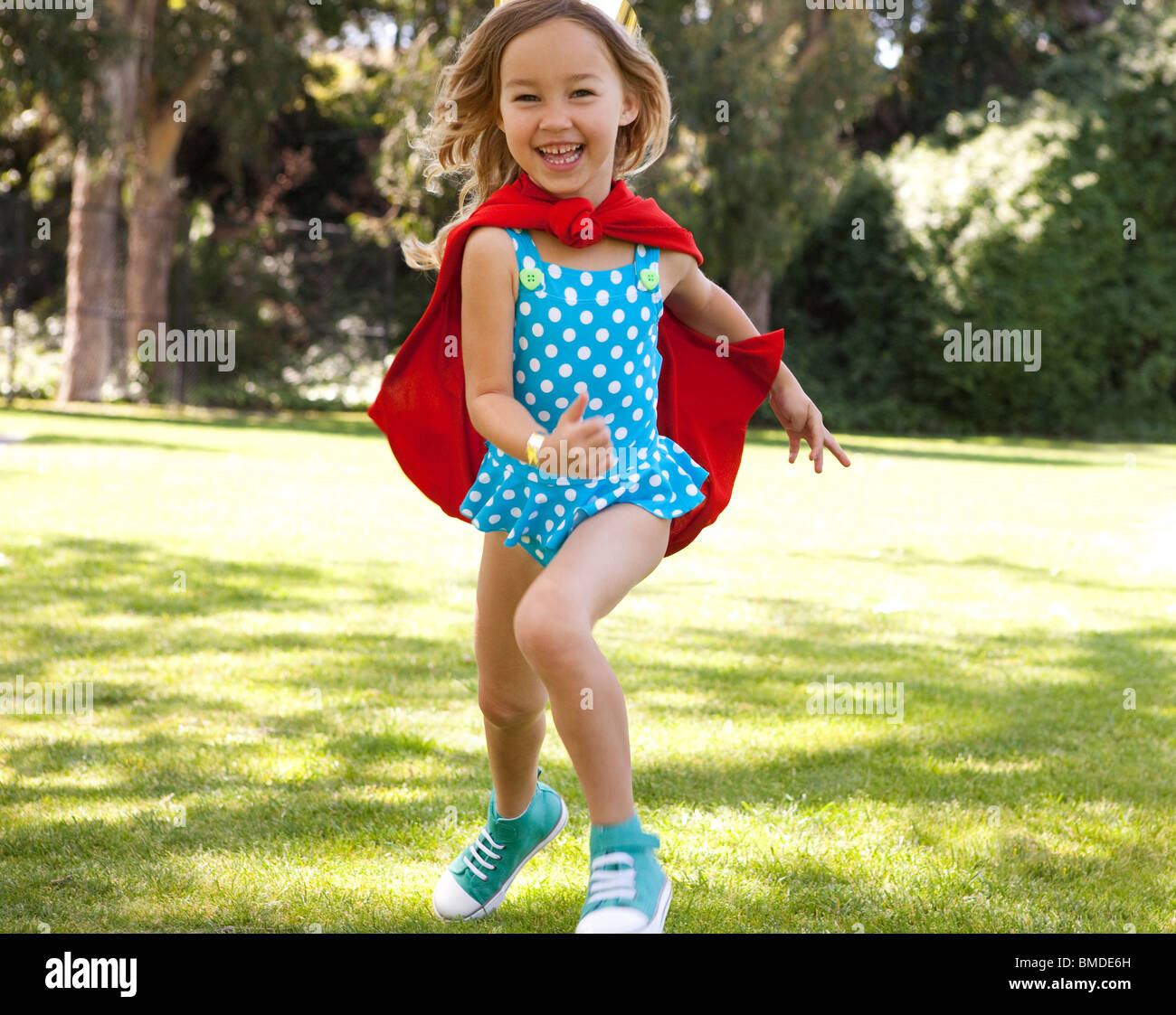 Girl in polka dot bathing suit and red cape running - Stock Image